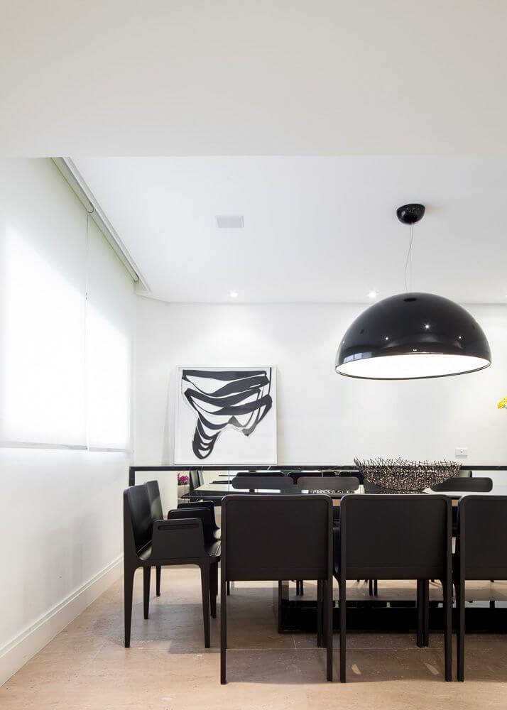 The formal dining room has light beige tile floors and crisp white walls. The modern dark wood dining set has two chairs at the heads of the tables, and is perfectly sized for a family gathering.