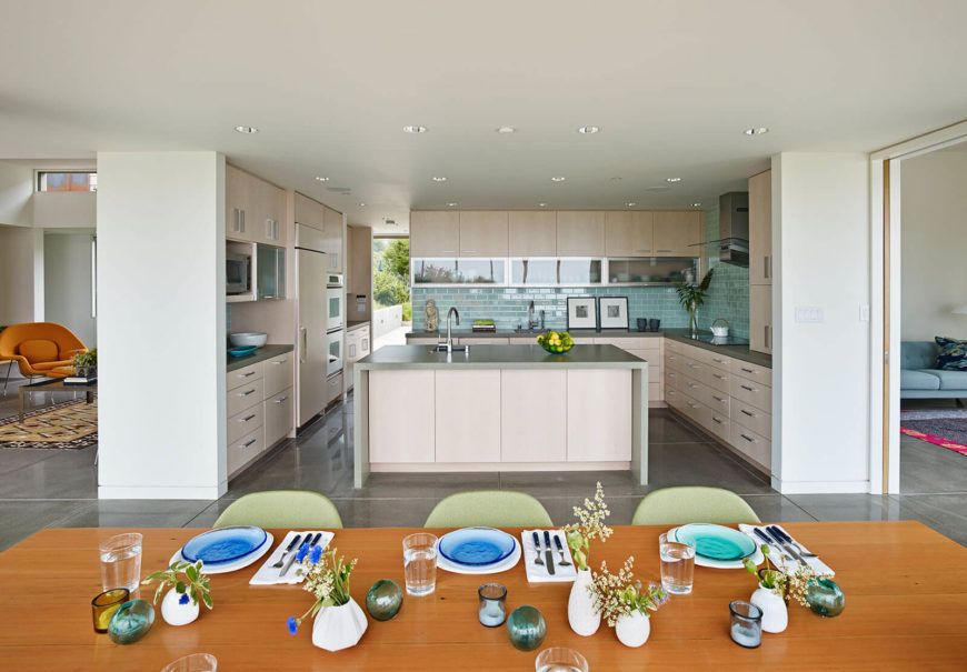 The kitchen is highlighted by aquamarine tile backsplash and sleek beige cabinetry. A large island centers the open space.