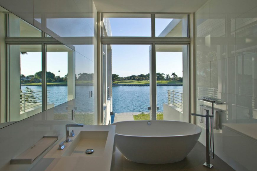 A white bathroom with a free-standing soaking tub positioned near an expansive window that looks out on the water. Sleek white tiles and vanity in white let the view take precedence over everything else.