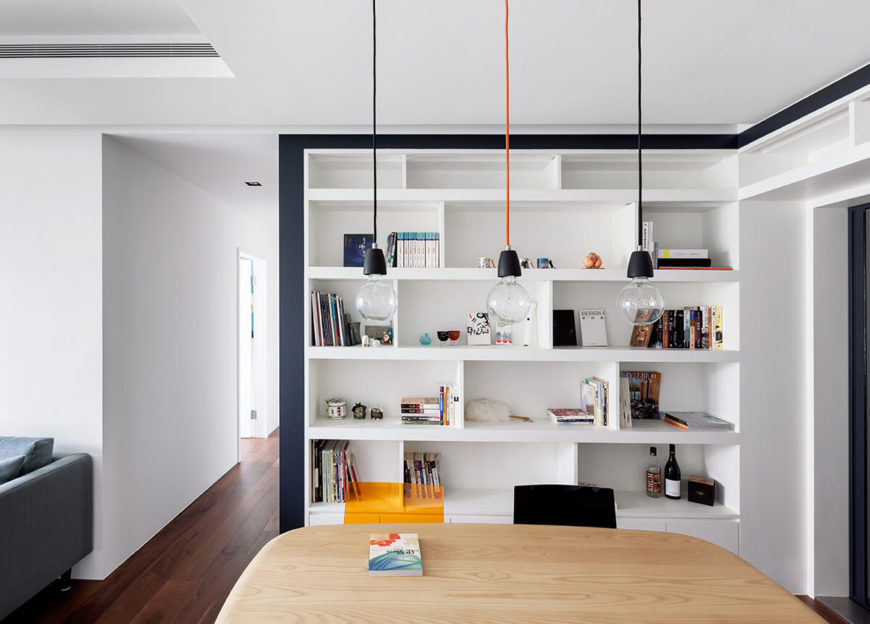 Across the dining table, we see the wall with built-in asymmetrical shelving, displaying the owners' books and other nicknacks. A trio of pendant lights hang at center.