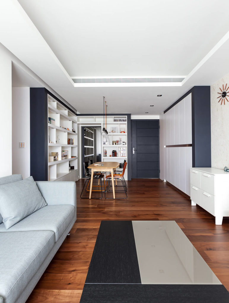 The open-plan design allows the compact home to feel much larger. Rich hardwood flooring contrasts with the stark white and black hues on the walls, while abundant shelving and cabinetry keep things organized.