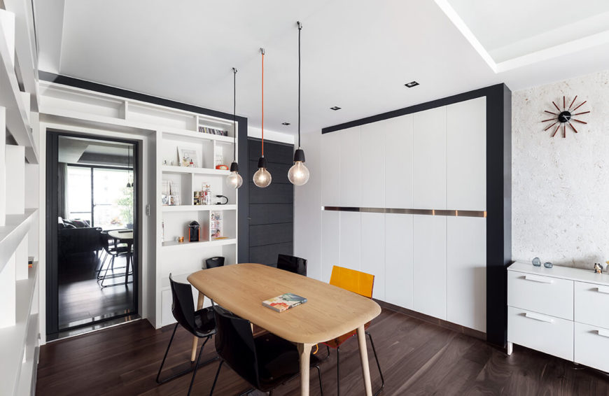 The dining room space exemplifies the mixture of white and dark hues throughout the home, with the dominant lighter shade defined by contrast. Rich natural wood table stands over deep hued hardwood flooring.