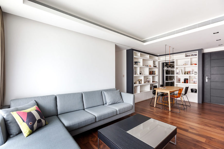 The expanse of white upon the ceiling and walls serves to heighten the subtle detail of aspects like the modern coffee table with glass panel and light hued sectional.