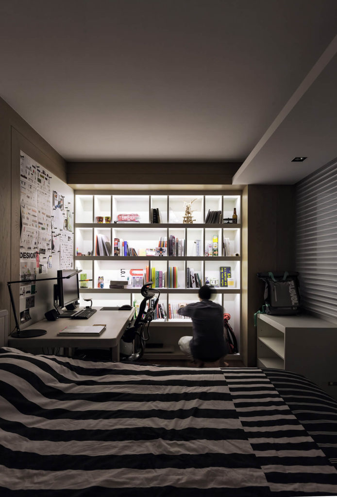 Here we have one of the bedrooms, aglow from shelving-mounted lighting. A full work desk and bed share the cozy space.
