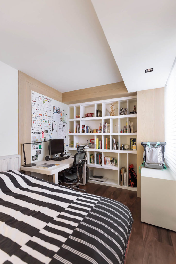 Here we see the bedroom in the light of day, bright and full of contrast, with rich dark hardwood flooring and lighter toned natural wood flanking the shelving.