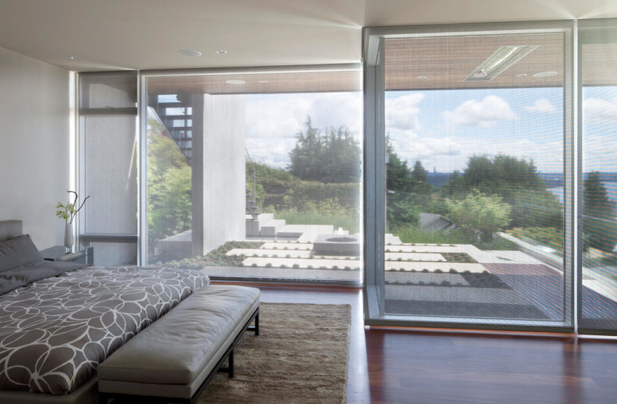 Gray master bedroom surrounded with glass walls covered by blinds. It has a tufted bed with floral pattern bedding and an upholstered leather bench on its end over a shaggy rug.