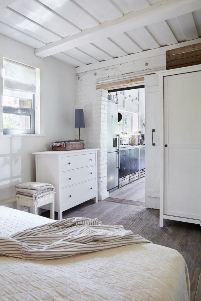 Around the white dining room wall, we find a bedroom continuing the theme of white on hardwood flooring. Intricate wood panel ceiling hangs above.