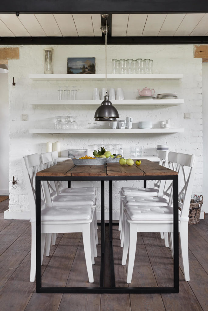 The dark metal and rich wood table creates a beautiful contrast in the white space, over aged, lighter hued hardwood flooring.