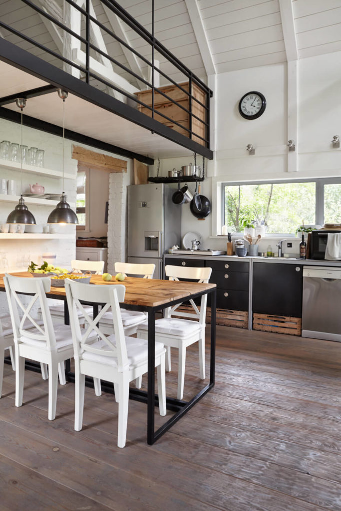 The black railings above mirror the table construction below, as well as the sleek black lower kitchen cabinets.