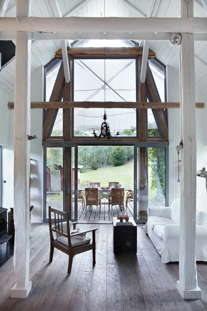 Across the expanse of hardwood flooring we see the grand, full height windows over the doorway. The terrace extends naturally from the interior, with a full dining set outdoors.