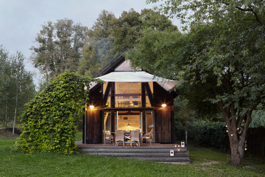 The original barn structure has been completely gutted and redone, with rustic styled wood wrapping the exterior. Vertical expanses of windows open the interior up.
