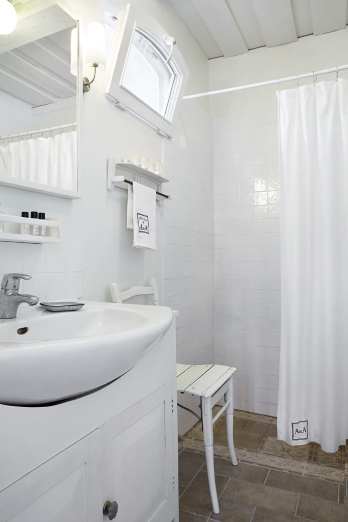 In front of the open-design shower we see the unique hybrid pedestal sink with white cabinetry built around it.