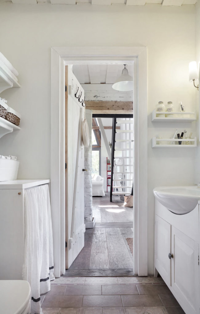 The bathroom is filled with white tones, as the rest of the home, but placed over tile flooring.