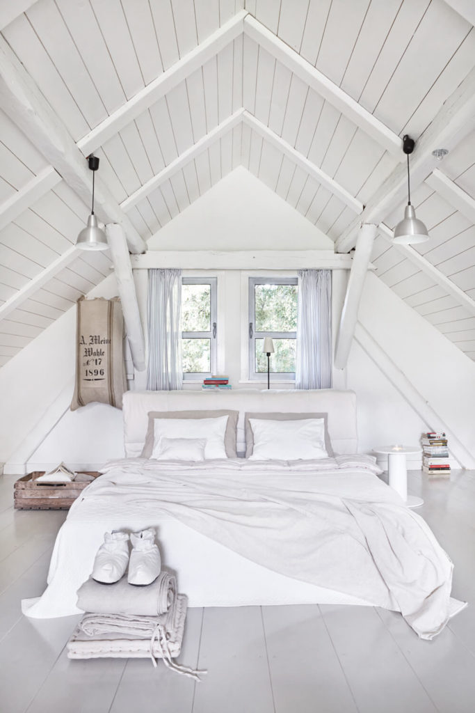 Upstairs, the loft holds the master bedroom at center, beneath the vaulted ceiling.