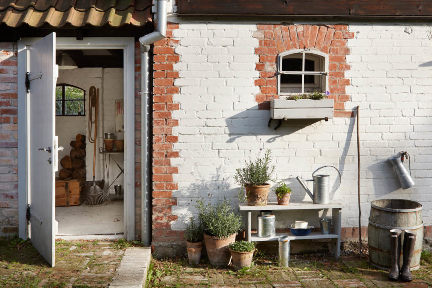 At the rear of the home, we see this brick structure, dotted with pottery and gardening supplies.