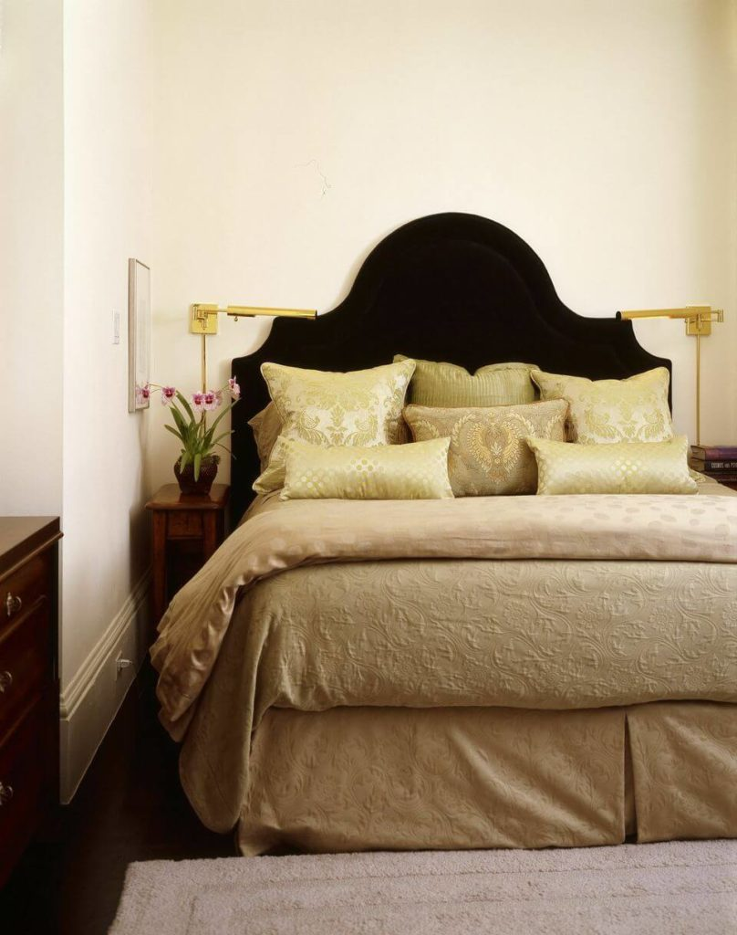 The home's other bedroom is a little more subtle, in a lightly patterned soft beige. Swiveling golden side lamps are attached to the wall, saving real estate on the small nightstands.
