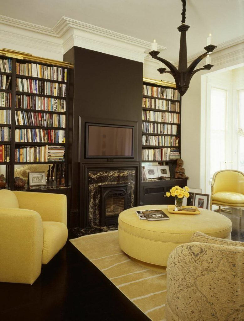 From this angle we can better see the salvaged wood bookcases on either side of the fireplace. The white tips of the dark chandelier mimic the way the dark bookcases and fireplace meet the white crown molding.