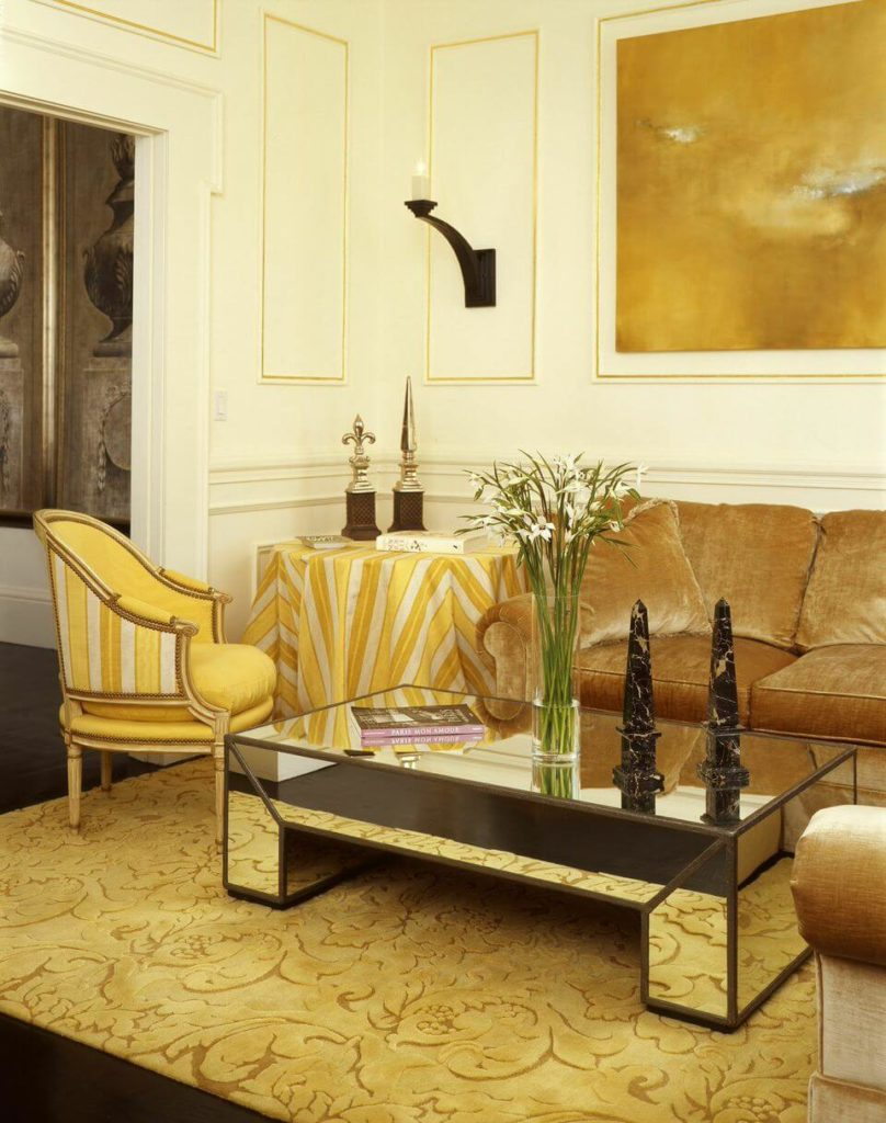 The main seating area of the living room consists of a light gold sectional sofa with a luxurious sheen and a small nail-trim armchair in yellow stripes. A small side table is covered in a matching fabric. The mirrored coffee table sits on an imported yellow rug from Nepal.