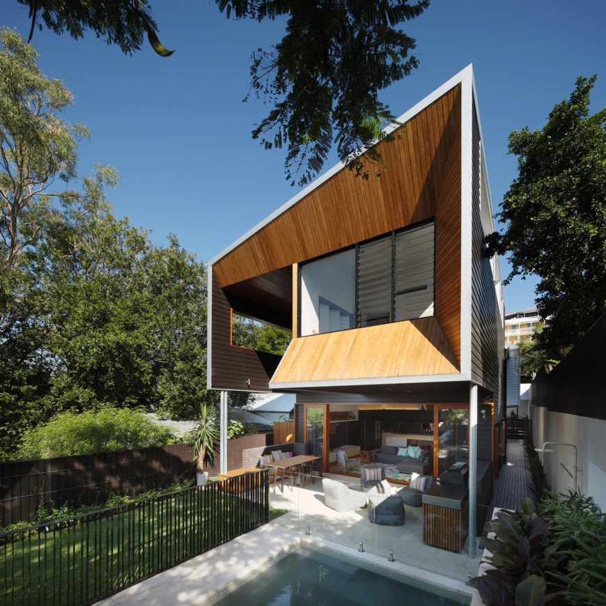 In the full view of the home exterior, we see the bedroom extension looming over a sheltered patio space, connecting directly to the living room via retractible sliding glass panels.