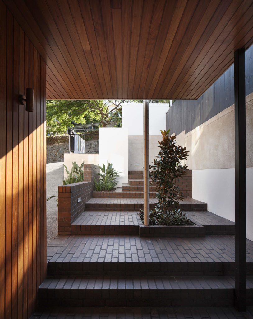 Here's a glimpse out the front of the home, showing the immense sense of privacy and coziness granted by the home's placement in the landscape. Concrete, brick, and rich wood panels create a timeless mixture.