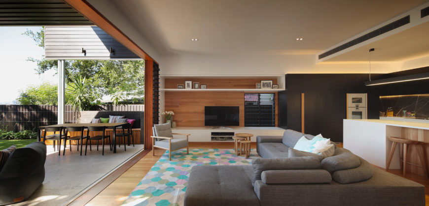 A wide profile view showcases the flow from outdoors on into the home, with natural wood and charcoal tones visually connecting the progression. The open-plan interior seamlessly blends the living and kitchen spaces.