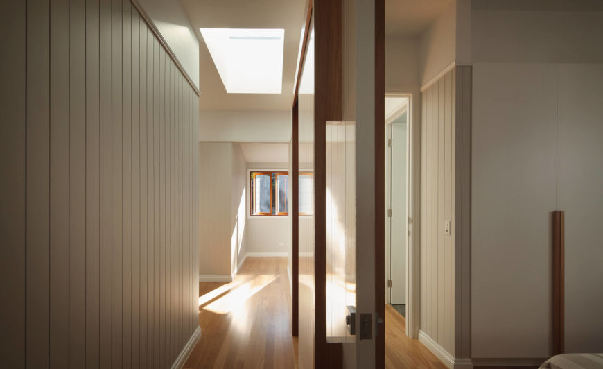 This upper floor hall continues the swath of rich hardwood flooring, beneath textured walls and abundant natural light, courtesy of skylights throughout.
