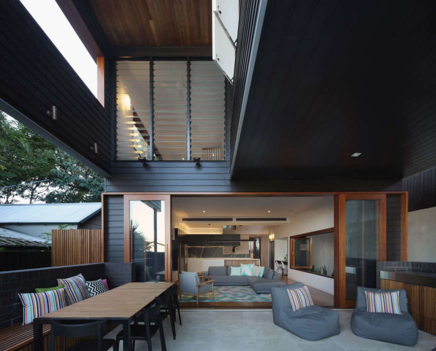 The large, sheltered patio space includes a full dining set and relaxing chairs matching the tones of the interior. This helps blur the line between indoors and out.