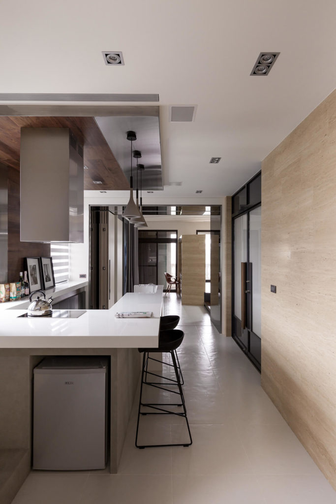The lengthy, narrow space allows for a variety of functions to share a single open-plan area, with the kitchen here giving way to a bedroom focused space in the distance.