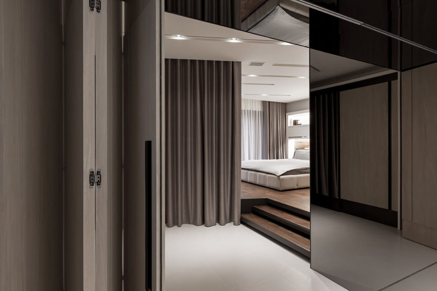 Seen through the retractable doors at the end of the kitchen, the bedroom holds a large dividing curtain for privacy.