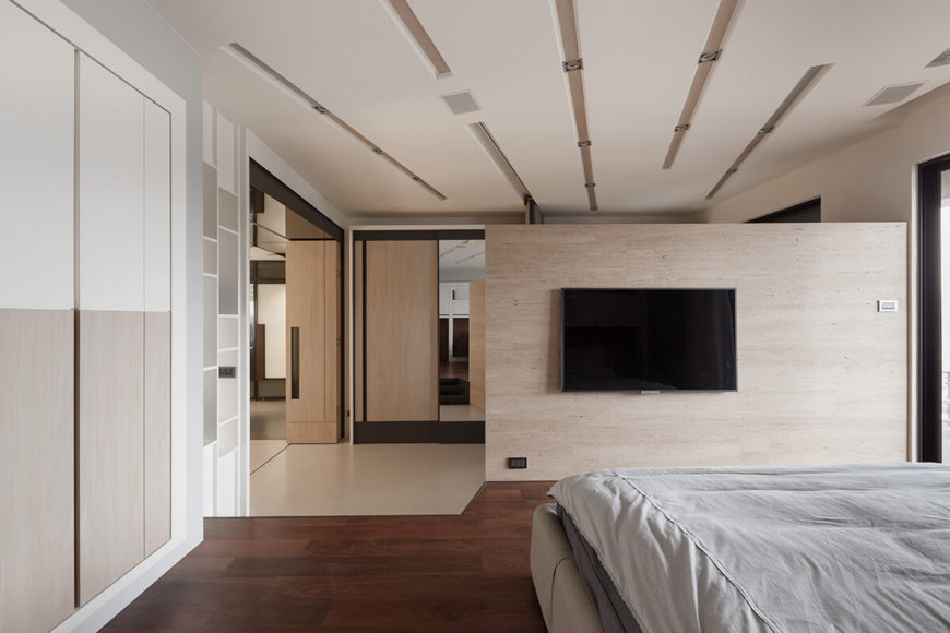 Viewed from the bed area, the dividing wall sleekly houses the Tv, while making for a private space within the en suite.