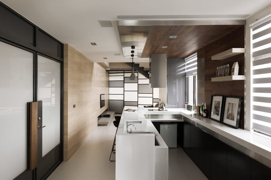 The kitchen itself features a U-shaped countertop in glossy white, with sleek black cabinetry for contrast. Panels of rich hardwood form a bold center on wall and ceiling.