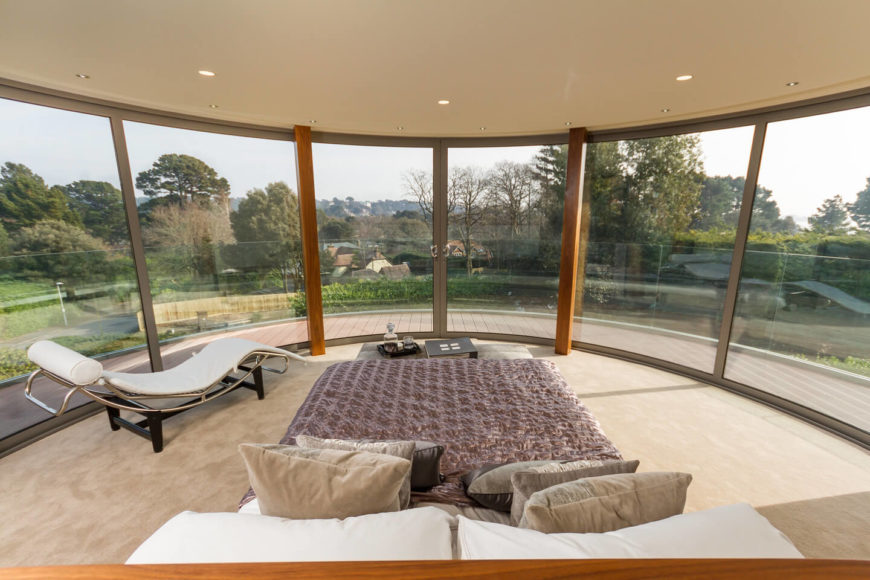 The master bedroom, on an upper floor, enjoys panoramic views courtesy of the wraparound full height glazing and unobstructed surroundings. The simple, cleanly designed room features a small table at the foot of the bed, and ultra-modern chaise lounge at left.