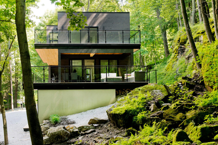 With a low view of the side, we can witness the high contrast look of the angular structure, rising from the natural green slope. Wraparound black metal and glass railings add safety without obscuring the view.