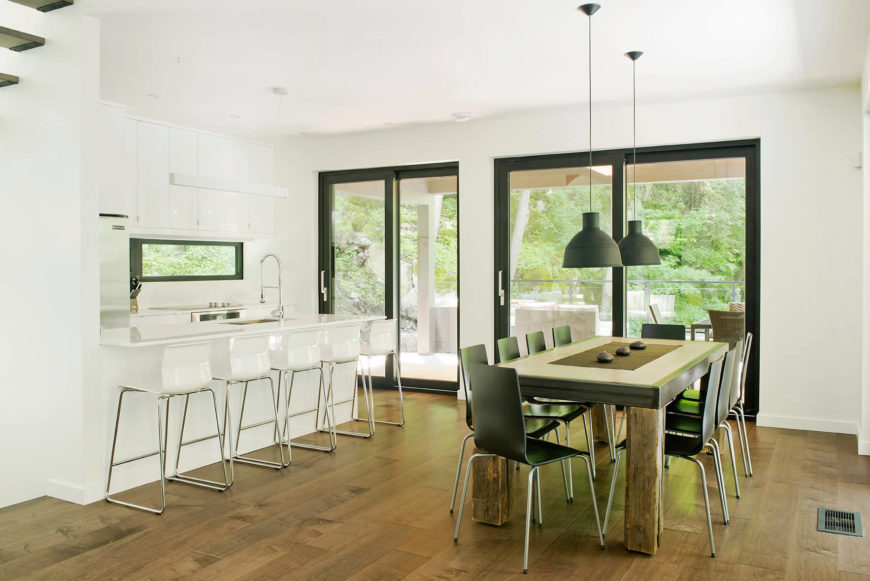 The dining space stands next to the ultra-modern kitchen, in pristine white. The rich hardwood flooring connects the entire area, anchoring the disparate styled furniture.