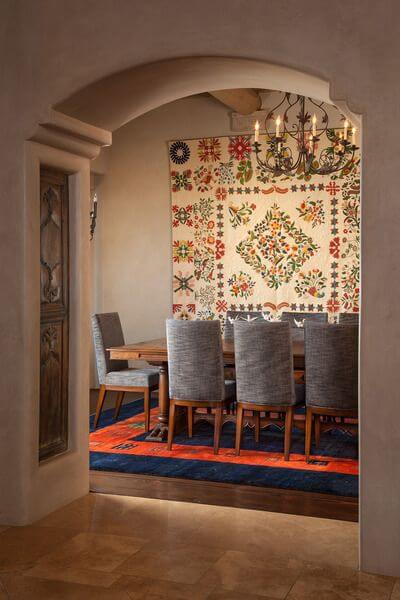 A shot into the dining room from the living room, showing the tile meeting the dark hardwood flooring. The custom-made dining table is surrounded by chairs upholstered in heather-gray. Beneath the table is a rug in deep navy and red-orange. On the back wall is an enormous hand-crafted quilt.