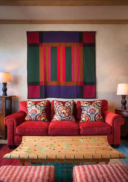 The family room is in an even bolder color and pattern scheme than the rest of the home, with a bright red-pink sofa, red and white patterned chairs, and a large quilt hanging above the sofa. The wooden coffee table has small, but colorful details.