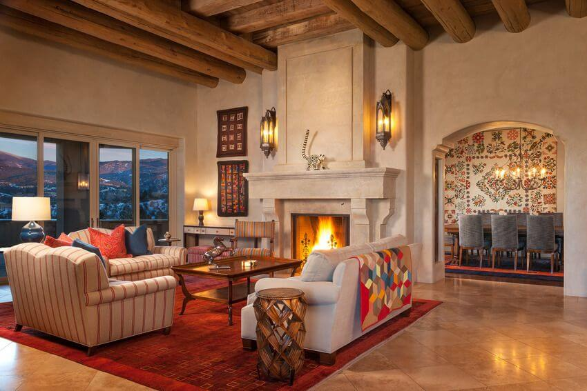 Another view of the living room, showing the cathedral ceilings that boast a network of thick wooden beams. A stately screened stone fireplace takes center stage between two antique wall sconces. Sliding glass doors lead outside to a terrace that overlooks the mountains.