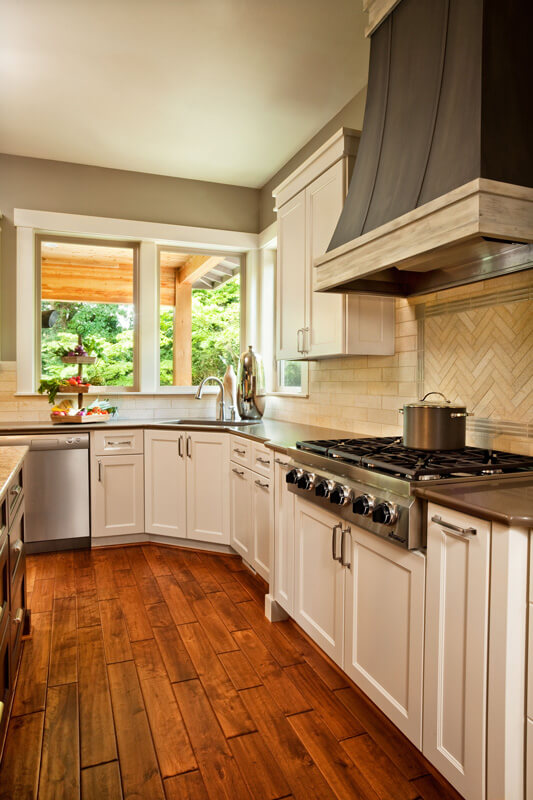 The contrast between soft white cabinetry, dark countertops, and warm hardwood flooring makes for a visually impressive kitchen space. Beige brick backsplash tile complements the style, along with stainless steel appliances.