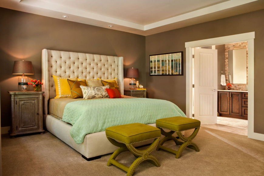 With a pair of white double doors leading to the en suite bathroom, the master bedroom expands its footprint. A pair of green hued ottomans stand at the foot of the bed.