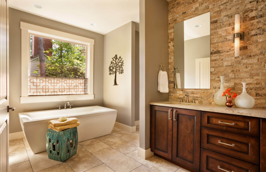 The expansive master bath spreads over large format tile flooring, with contemporary soaking tub beneath a large window at left, and other facilities tucked around a private corner at center.