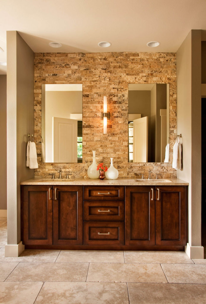 Rich wood double vanity in the master bath is topped with a granite countertop, while frameless mirrors hang on the stone brick wall above.