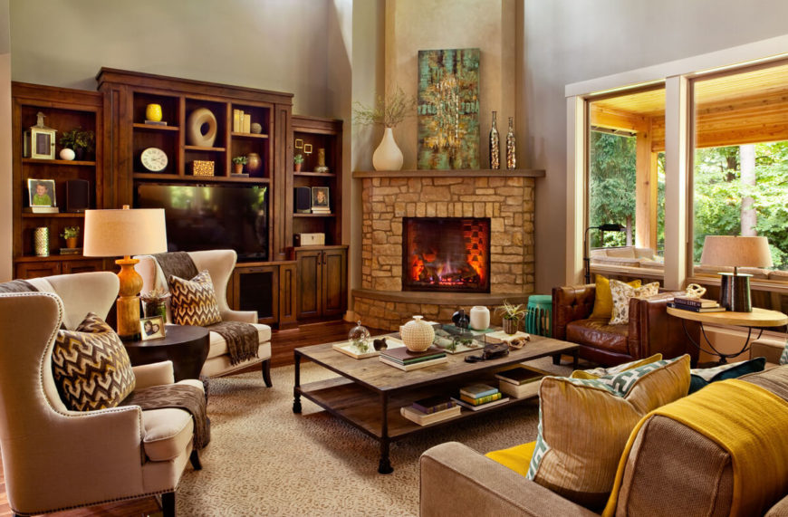 The living room centers a raft of rich furniture around a two-tiered rustic coffee table and large corner fireplace wrapped in stone. The abundance of rich natural wood hues complements the beige area rug and high back armchairs.