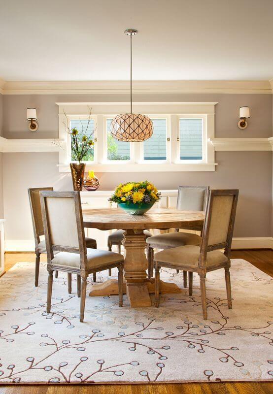 Gray dining room features a round dining table and wooden chairs illuminated by a lovely pendant and wall sconces.