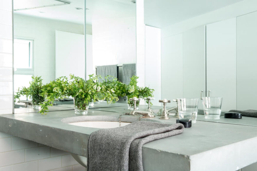 A second bathroom boasts a unique floating concrete vanity, with corner mirrors and white brick tile.