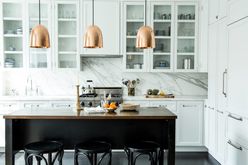 The kitchen boasts an array of glass door cabinetry over marble backsplash. A trio of copper pendant lights hangs above a large black table with natural wood surface.