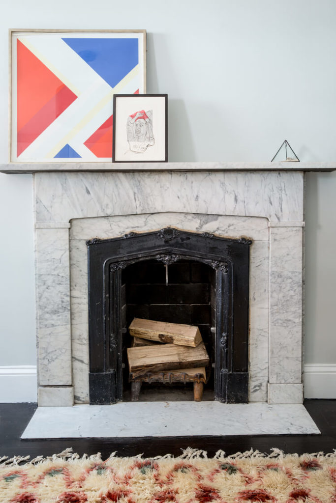 The fireplace stands in bright, rich marble over the dark hardwood flooring. A slim mantle above the compact fireplace holds art pieces.