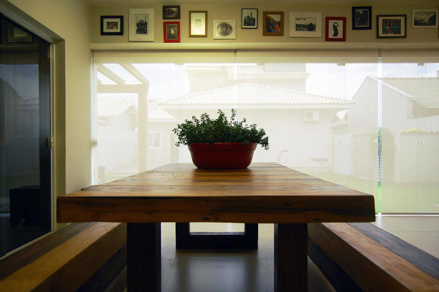 The massive wood dining table features a metal frame and fixed-bench seating. Above the windows we see many of the framed photographs that wrap this space.