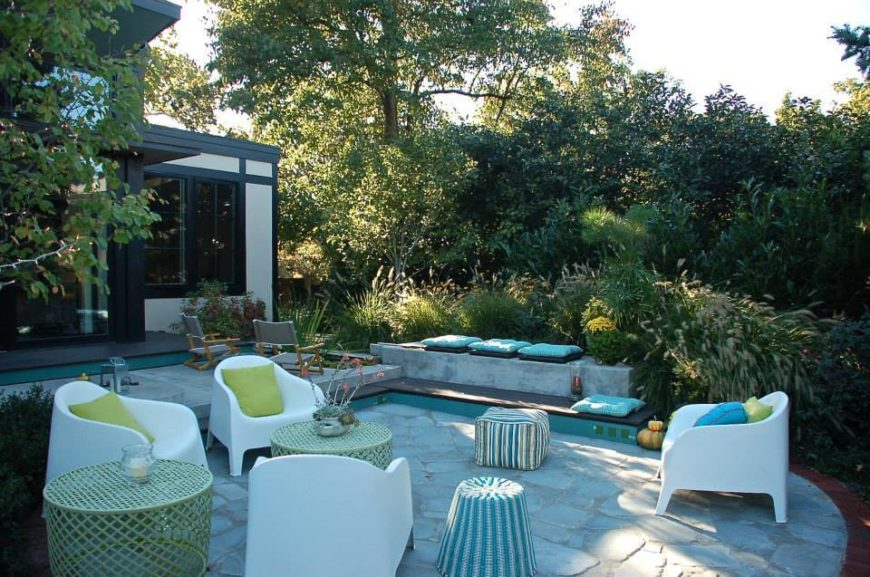 The back patio shares a host of unique seating options, with white armchairs and wicker tables ensconced in lush greenery behind the home.