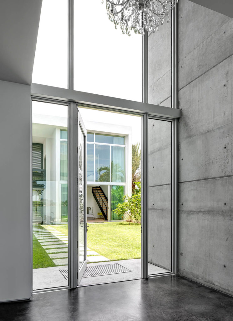 The contemporary concrete construction frames elaborate arrays of full height glass, seen here in the private entrance of the home. The bedroom segment of the home is visible across the central courtyard.