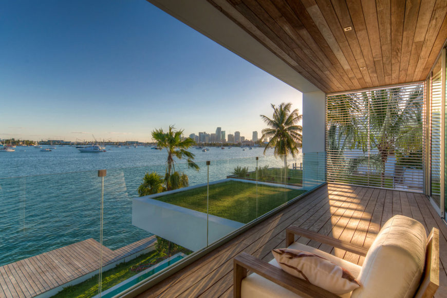The balcony, awash in rich timber and defined by a frameless glass wall, offers spectacular views across the bay. Rooftop lawn extension adds some natural presence to the modern structure.
